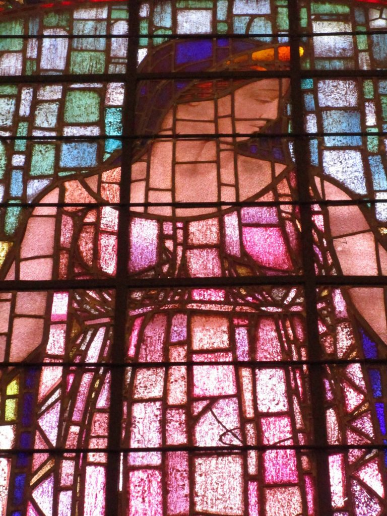 Robed female figure in stained glass