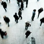 overhead view of blurred people walking through a large lobby